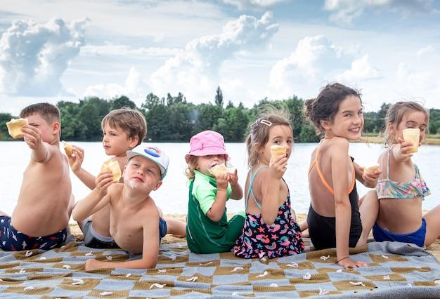 子供たちは川のそばの毛布に座り、泳いだ後はリラックスします。