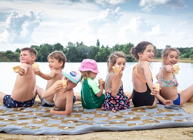 Дети сидят на одеяле у реки и расслабляются после купания.