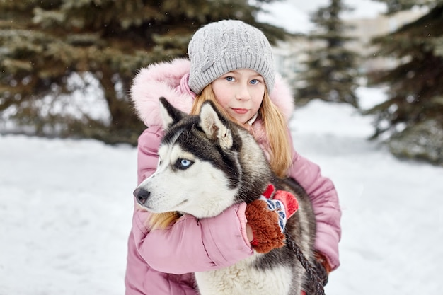 Children sit in the snow and stroked dog husky. children go out and play with husky dog in winter. walk in the park in winter, joy and fun, dog husky with blue eyes. russia, sverdlovsk, 28 dec 2017