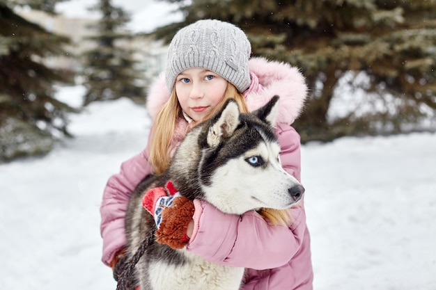 Children sit in the snow and stroked dog husky. children go out and play with husky dog in winter