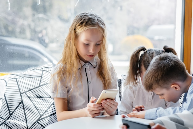 Children sit at a table in a cafe and play mobile phones together.