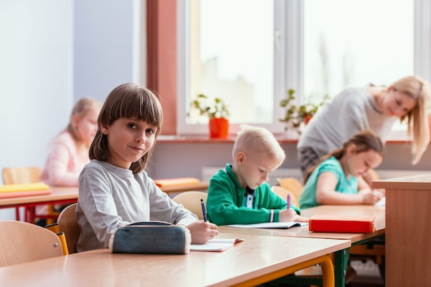 Children sit at the tables in the classroom waiting for the first lesson in the new school year