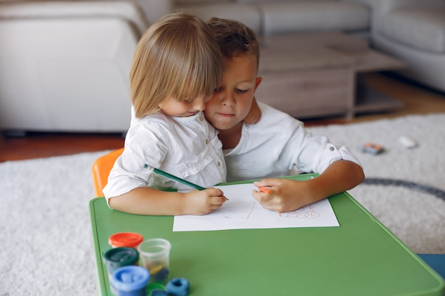 Children siting at the green table and drawing
