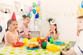 Children sitting at table on birthday