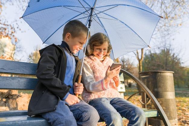 Children sitting on bench in autumn park, using smartphone