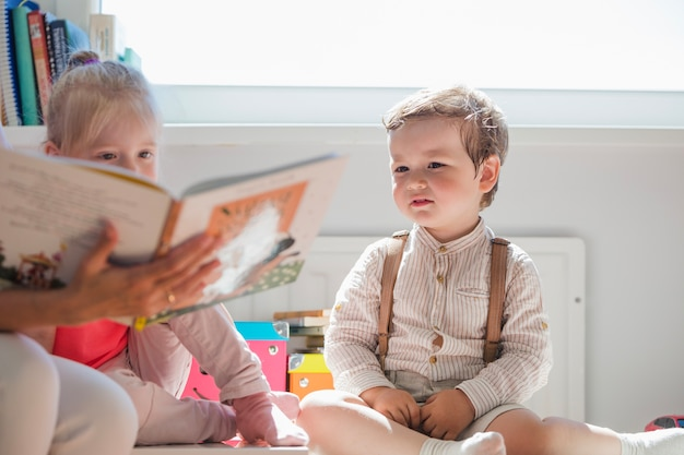 Children sitting looking at book