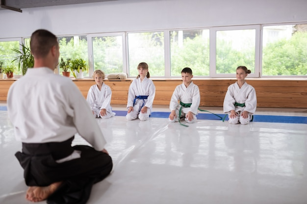 Children sitting near the window and listening attentively to their aikido trainer
