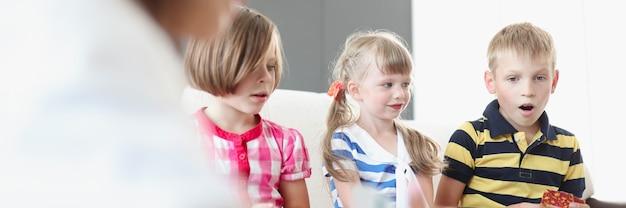 ソファに座って両親とボードゲームをしている子供たち