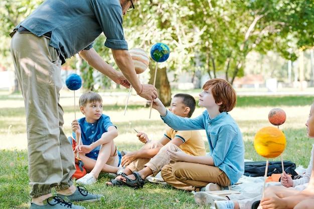 Дети сидят на зеленой траве и держат в руках модели планет, наслаждаясь уроком астрономии на открытом воздухе при солнечном свете