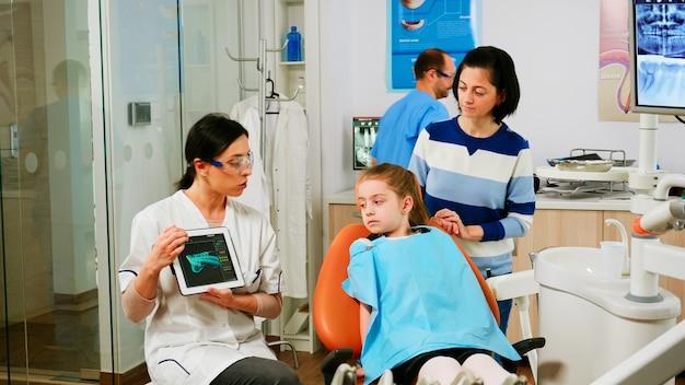 歯科医院でタブレットを探している小児科医を聞いている口腔病学の椅子に座っている子供たち。歯科医ユニットで現代のガジェットを使用して子供の歯のレントゲン写真の母親に見せている歯科医