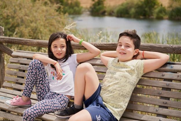 池を背景に公園でリラックスして笑っている木製のベンチに座っている子供たち