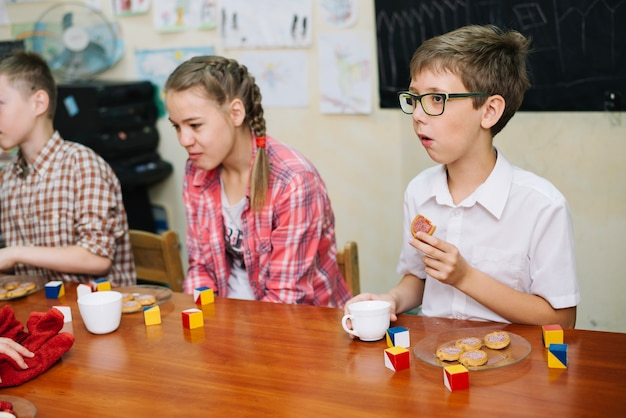 Children sitting at table eating biscuits drinking