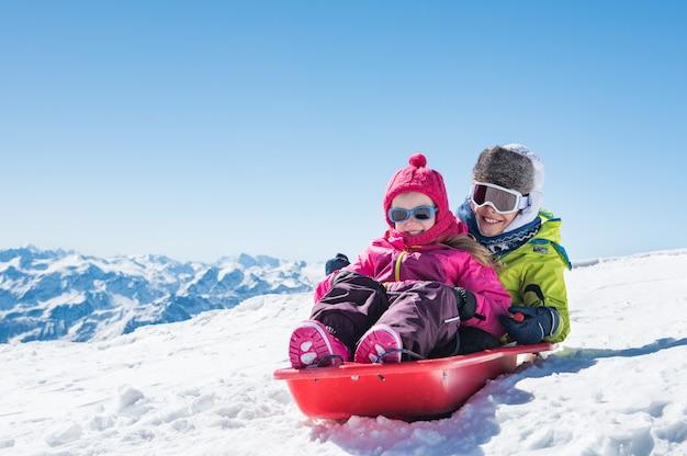 Детское катание на санях по снегу