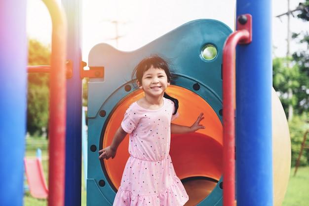 Дети улыбаются, весело, маленькая девочка, играющая на улице, счастливая в саду, сидя на детской площадке, международный день защиты детей.