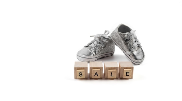 Children sneakers on wooden cubes with the word sale