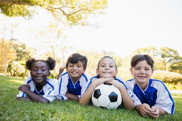 Children soccer team smiling while lying on the floor