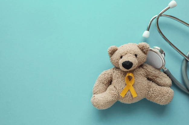 イエローゴールドのリボンと聴診器で子供のぬいぐるみヒグマ