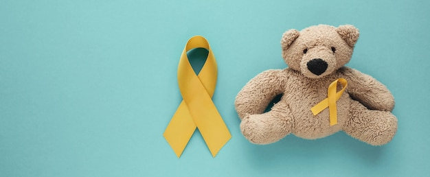 Children soft toy brown bear with yellow gold ribbon