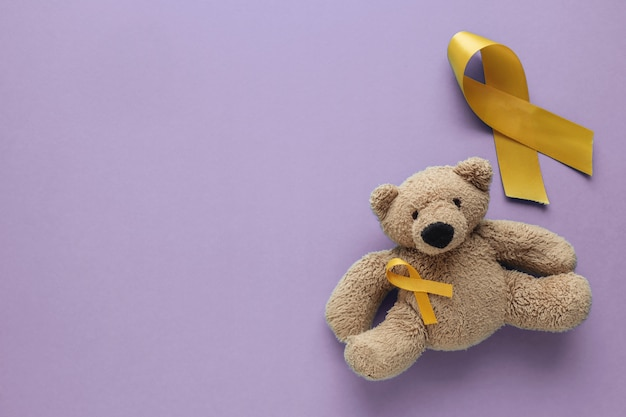 Children soft toy brown bear with yellow gold ribbons on purple background