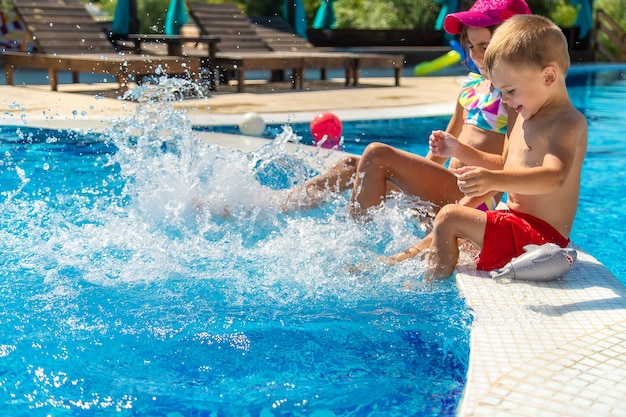 아이들은 수영장에서 발을 튀깁니다. 선택적 초점입니다.