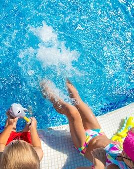 子供たちはプールで足で水をはねかけます。セレクティブフォーカス。キッズ。