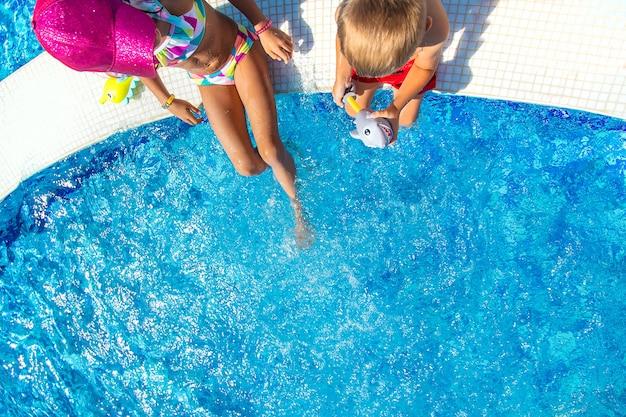 子供たちはプールで足で水をはねかけます。セレクティブフォーカス。