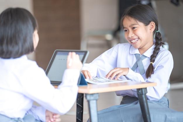 디지털 태블릿을 사용하여 함께 공부하고 학교에서 공책에 글을 쓰는 학생