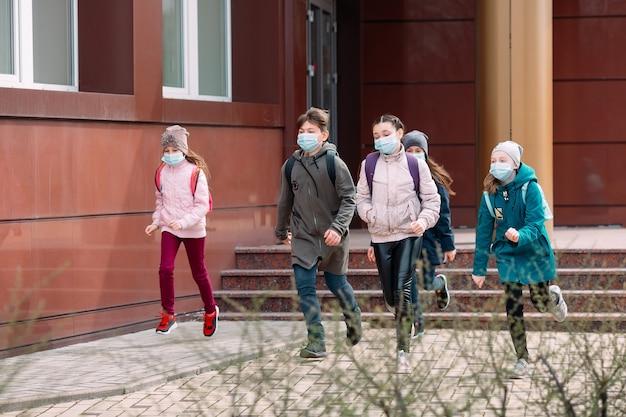 Дети-школьники в медицинских масках покидают школу.