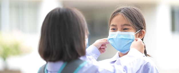 Дети-ученики в студенческой форме и в защитных масках ходят друг для друга в школу после улучшения ситуации с пандемией covid-19. снова в школу stock photo