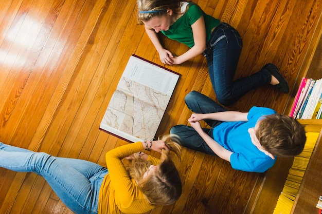 Children studying map sitting on floor