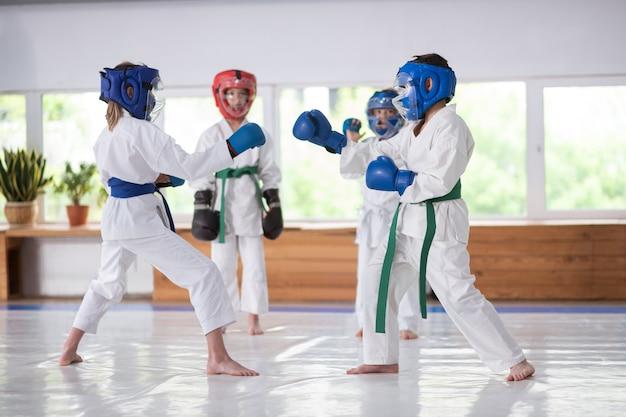 Дети изучают боевые искусства в шлемах во время бокса