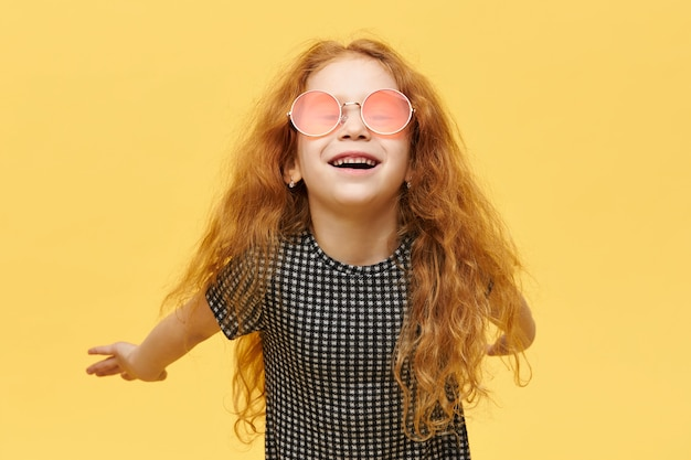 Children, style and fshion concept. carefree fashionable little girl with curly red hair having happy joyful facial expression, laughing, wearing stylish pink sunglasses, keeping arms behind her back