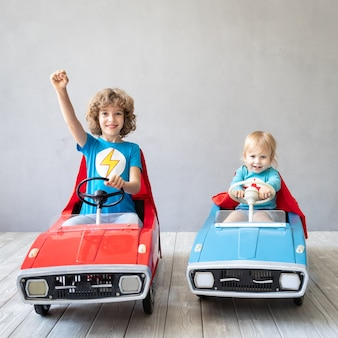 Children superheroes playing at home
