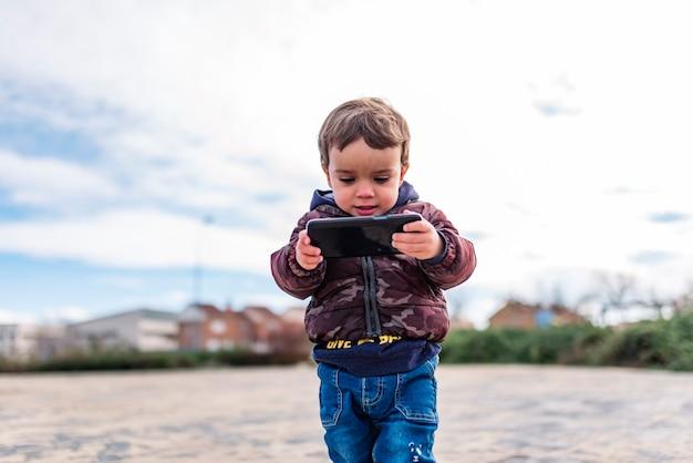 휴대 전화로 야외에서 인터넷을 서핑하는 어린이