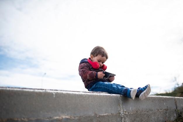 Дети серфинга в интернете на открытом воздухе на мобильном телефоне