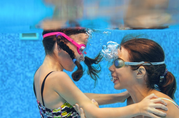 Children swim in pool underwater, happy active girls in goggles have fun in water, kids sport on family vacation