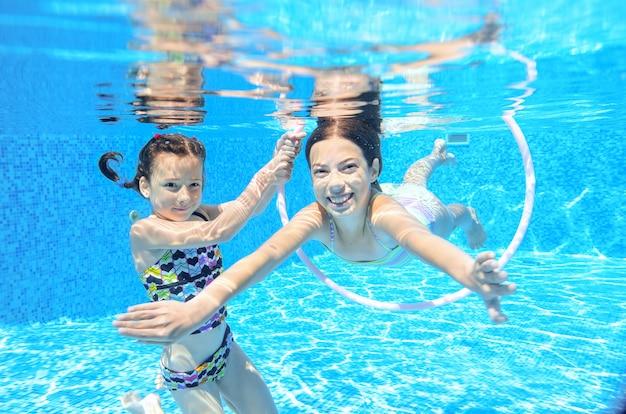 Children swim in pool underwater, happy active girls have fun under water, kids sport on family vacation