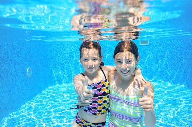 Children swim in pool underwater, happy active girls have fun under water