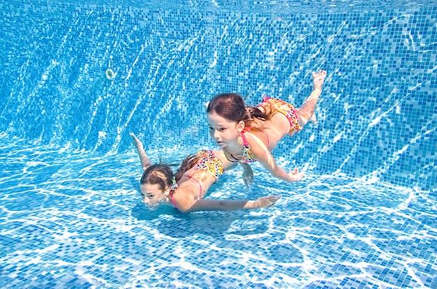 Children swim in swimming pool underwater little active girls have fun under water kids fitness