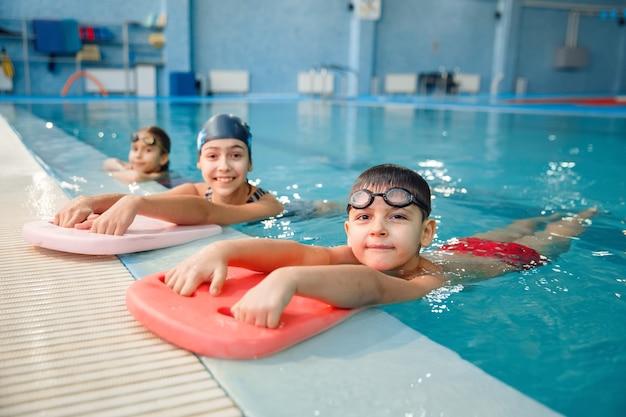 Детская плавательная группа позирует у бассейна