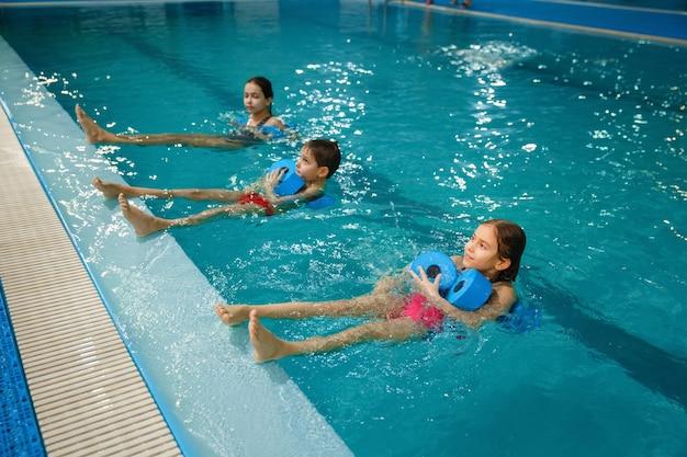子供たちの水泳グループ、プールでダンベルを使ったトレーニング