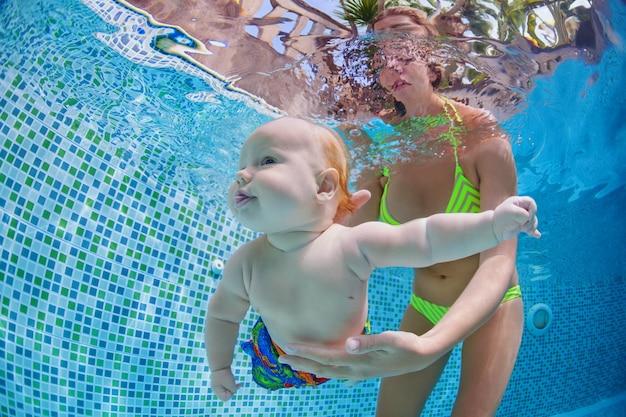 Детский урок плавания - бэби-бот с мамой учатся плавать, ныряют под воду в бассейне.