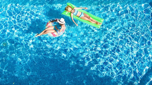 Children in swimming pool aerial drone view from above happy kids swim on inflatable ring donut