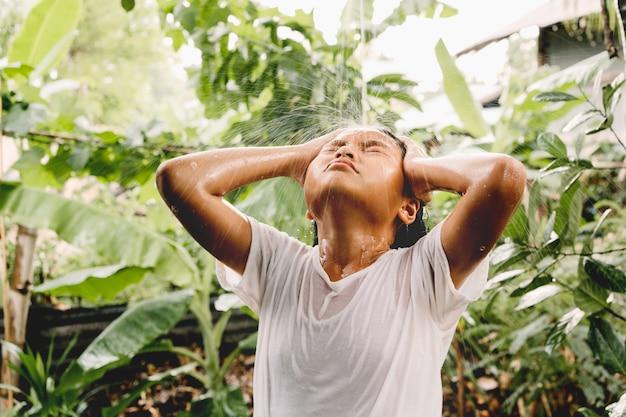 Дети купаются с летним дождем на зеленой природе