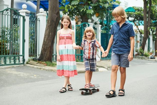 Children teaching boy skateboarding