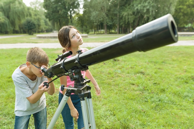 Children teenagers in the park looking through a telescope