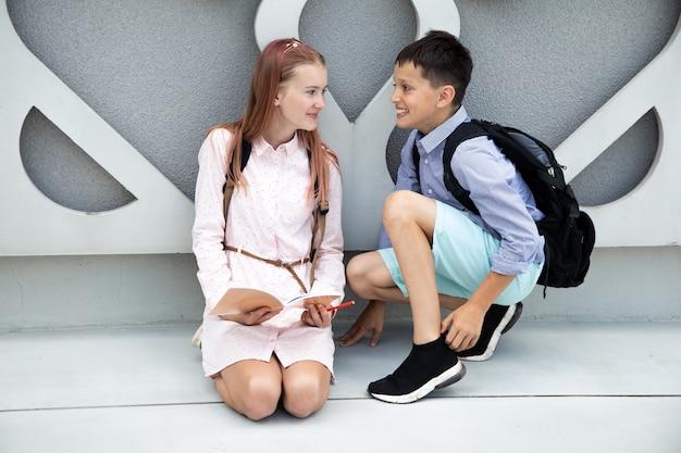 Дети подростков школьники мальчик и девочка на фоне бетонной стены дети смеются с ...