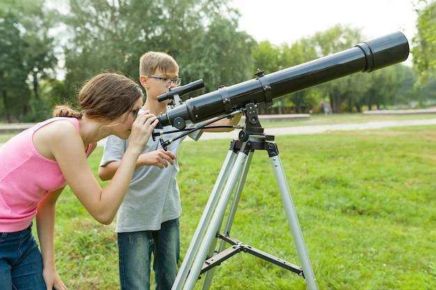 望遠鏡で子供10代の若者は、自然の空を見てください。