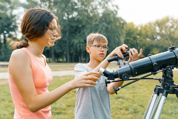 Children teenagers with telescope look at the sky in nature