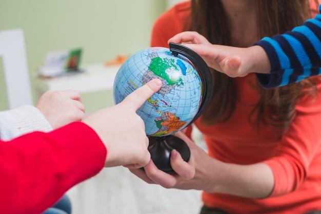 Children touching globe